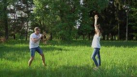 Przystojny mężczyzna bierze fotografie z kamerą młody szczęśliwy kobieta w ciąży w parku zbiory wideo