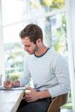 Przystojny mężczyzna bierze notatki na schowku Obraz Royalty Free