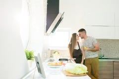 Przystojny mężczyzna całowania żony kucharstwo w kuchni zdjęcia stock