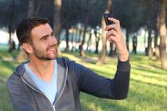 Przystojny mężczyzna chapie pic z jego telefonem komórkowym obrazy royalty free