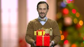 Przystojny mężczyzna daje Bożenarodzeniowym prezentów pudełkom zbiory