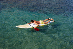 Przystojny mężczyzna dopłynięcie na surfboard przy jasną wodą Obraz Royalty Free