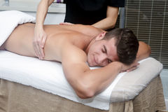 Przystojny mężczyzna dostaje masaż w zdroju Zdjęcie Stock