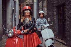 Przystojny mężczyzna i seksowna elegancka dziewczyna chodzimy z retro Włoskimi hulajnoga wzdłuż starych ulic miasto fotografia stock