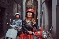 Przystojny mężczyzna i seksowna elegancka dziewczyna chodzimy z retro Włoskimi hulajnoga wzdłuż starych ulic miasto zdjęcia stock