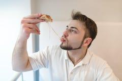Przystojny mężczyzna je gorącego kawałek pizza Mężczyzna je ser który rozciąga out z plasterkiem pizza Obrazy Stock