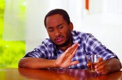 Przystojny mężczyzna jest ubranym białego błękitnego koszulowego obsiadanie baru kontuarem kłama nad biurkiem wyraża żadny pragni Fotografia Royalty Free
