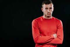 Przystojny mężczyzna jest ubranym czerwonego sportswear i pozuje po ćwiczeń na ciemnym tle Zdrowy inspiracyjny sprawność fizyczna Obraz Royalty Free