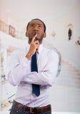 Przystojny mężczyzna jest ubranym koszula i krawat pozuje mienie telefon komórkowego w ręce podczas gdy rozważny język ciała Obrazy Royalty Free