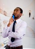 Przystojny mężczyzna jest ubranym koszula i krawat pozuje mienie telefon komórkowego w ręce podczas gdy rozważny język ciała Obraz Stock