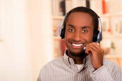 Przystojny mężczyzna jest ubranym przypadkowych ubrania i słuchawki z mikrofonem, wielka pozytywna postawa ono uśmiecha się kamer zdjęcia royalty free