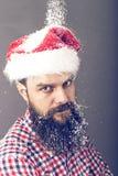 Przystojny mężczyzna jest ubranym Santa nakrętkę z długą brodą Fotografia Royalty Free