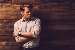 Przystojny mężczyzna jest ubranym w kratkę koszula w drewnianym wiejskim domowym wnętrzu obrazy stock