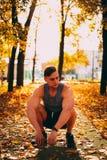 Przystojny mężczyzna kucanie w jesień parku w sportswear fotografia stock