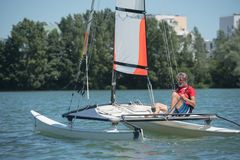 Przystojny mężczyzna ma zabawę z catamaran na jeziorze Obraz Stock