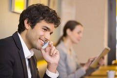 Przystojny mężczyzna na telefonie komórkowym w kawowym barze Obraz Stock