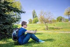 Przystojny mężczyzna na trawie z telefonem na słonecznym dniu Obraz Stock