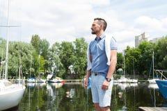Przystojny mężczyzna na wakacje z jachtami na rzecznym molu i lesie fotografia stock