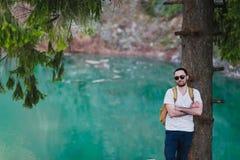 Przystojny mężczyzna nad zieloną naturą i błękitna jeziorna pozycja blisko drzewa Przygody, podróży, turystyki i czasu wolnego po obrazy stock