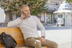 Przystojny mężczyzna obsiadanie na ławce i opowiadać na telefonie zdjęcia stock