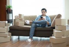 Przystojny mężczyzna obsiadanie na kanapie używać smartphone z kartonem zdjęcie stock
