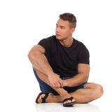 Przystojny mężczyzna obsiadanie na podłogowym i patrzeć daleko od obrazy stock