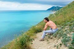 Przystojny mężczyzna obsiadanie na wzgórzu i patrzeć na morzu Boczny widok Zdjęcia Royalty Free
