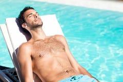 Przystojny mężczyzna odpoczywa na deckchair zdjęcie royalty free