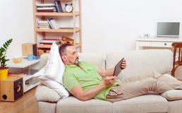 Przystojny mężczyzna odpoczywa na kanapie w domu Obrazy Royalty Free