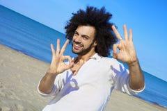 Przystojny mężczyzna ok znak na plaży obraz stock