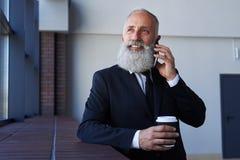 Przystojny mężczyzna opowiada na telefonie z popielatą brodą podczas gdy trzymający filiżankę Obraz Stock