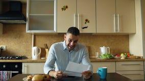 Przystojny mężczyzna otrzymywa dobre'u wieści czytania list w kuchni podczas gdy śniadanie wczesnego poranek w domu zdjęcie royalty free