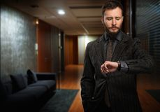 Przystojny mężczyzna patrzeje wristwatch Obraz Royalty Free