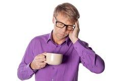 Przystojny mężczyzna pije filiżanka kawy stresującego się z ręką na głowie z szkłami nad białym tłem Migrena, zimno i grypa, obraz royalty free