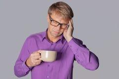 Przystojny mężczyzna pije filiżanka kawy stresującego się z ręką na głowie z szkłami nad szarym tłem Migrena, zimno i grypa, obrazy royalty free