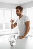 Przystojny mężczyzna Pije szkło świeża woda Indoors W ranku Zdjęcie Royalty Free