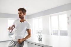 Przystojny mężczyzna Pije szkło świeża woda Indoors W ranku Zdjęcia Royalty Free