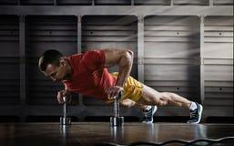 Przystojny mężczyzna podnosi ćwiczenie z jeden ręką w sprawności fizycznej gym robić pcha Zdjęcia Royalty Free