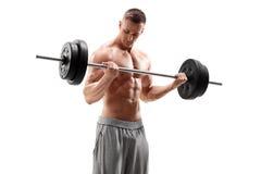 Przystojny mężczyzna podnosi ciężkiego barbell Zdjęcie Stock