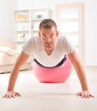 Przystojny mężczyzna podnosi na gym piłce robić pcha Zdjęcie Royalty Free
