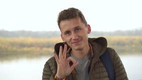 Przystojny mężczyzna pokazuje ok obok w ranek naturze, plenerowy, w górę portreta facet zdjęcie wideo