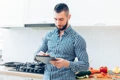 Przystojny mężczyzna pracuje w kuchni, przyglądającej up na internetów receipes Szczegóły nowożytny kucbarski działanie z pastylk Obraz Royalty Free