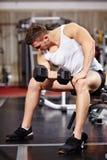 Przystojny mężczyzna pracuje z ciężkimi dumbbells w gym Zdjęcie Stock