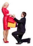 Przystojny mężczyzna przedstawia kobieta prezenty na kolanach Zdjęcia Stock