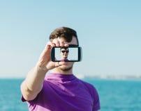 Przystojny mężczyzna robi autoportretowi z smartphone Obrazy Royalty Free