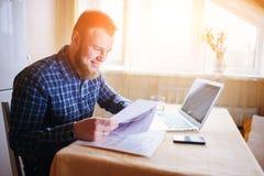 Przystojny mężczyzna robi niektóre papierkowej robocie w domu zdjęcia royalty free