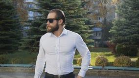 Przystojny mężczyzna stawia dalej okulary przeciwsłonecznych i zaczyna iść na alei 4K zdjęcie wideo