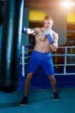 Przystojny mężczyzna trenuje na uderza pięścią torbie w gym w błękitnych bokserskich rękawiczkach Męski bokser robi treningowi Fotografia Royalty Free