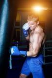 Przystojny mężczyzna trenuje na uderza pięścią torbie w gym w błękitnych bokserskich rękawiczkach Męski bokser robi treningowi Obraz Royalty Free