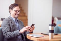 Przystojny mężczyzna używa mądrze telefon Obraz Stock